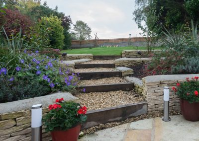 Green oak sleeper steps and Cotswold stone walling